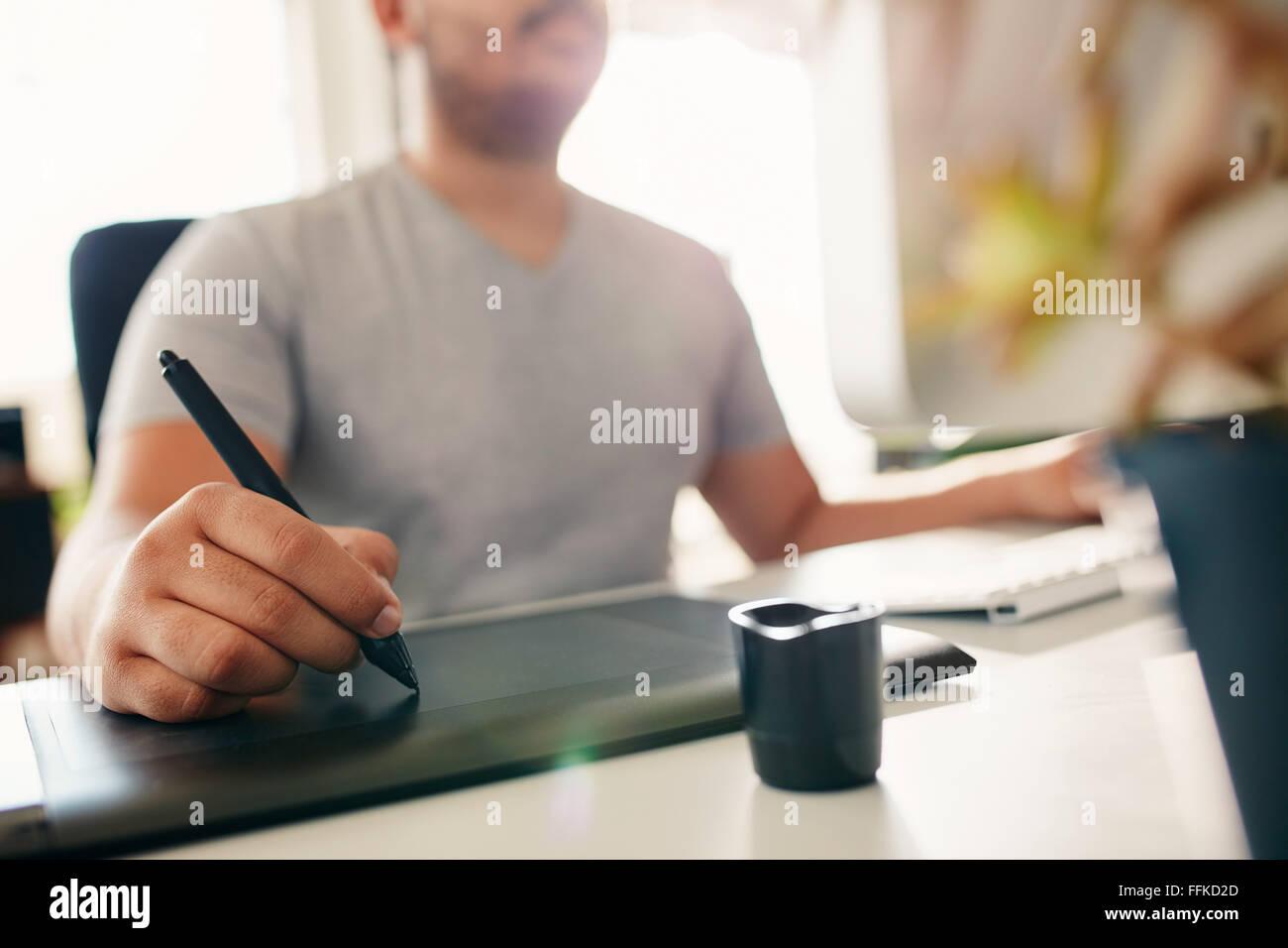 Mano de macho diseñador que trabaja en su escritorio utilizando el lápiz digital y tableta gráfica. Imagen De Stock