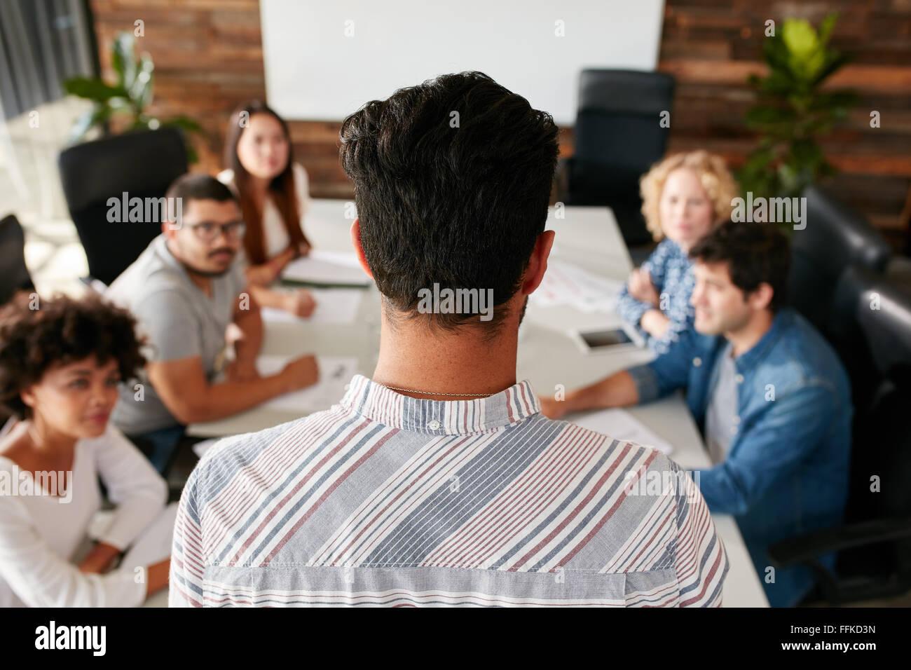 Vista trasera del retrato del hombre dando presentación del negocio a los colegas en la sala. Los jóvenes reunidos Foto de stock