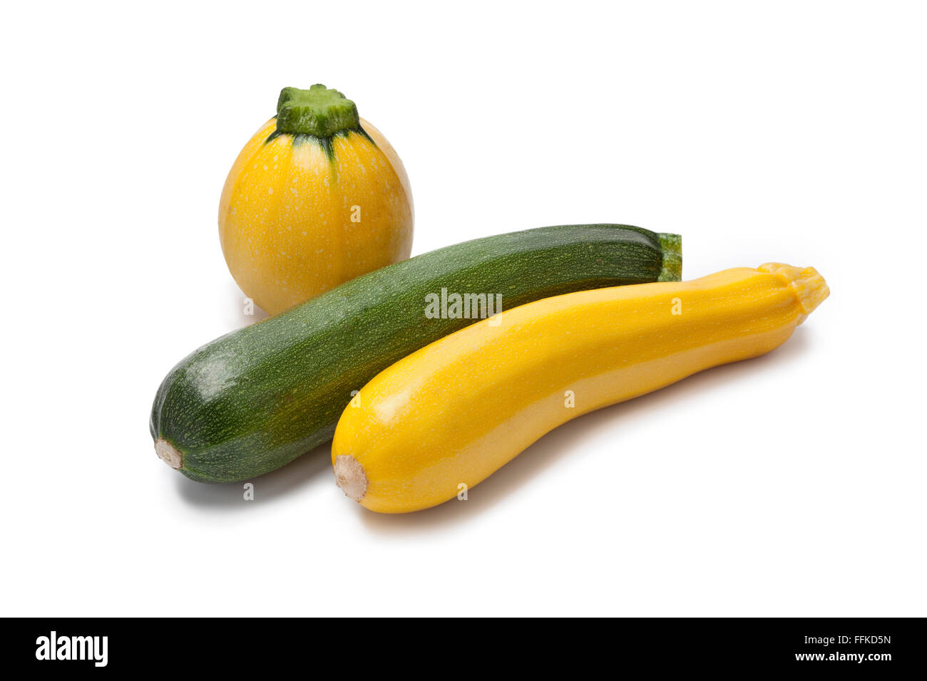 Amarillo, verde y calabacín redondo sobre fondo blanco. Imagen De Stock
