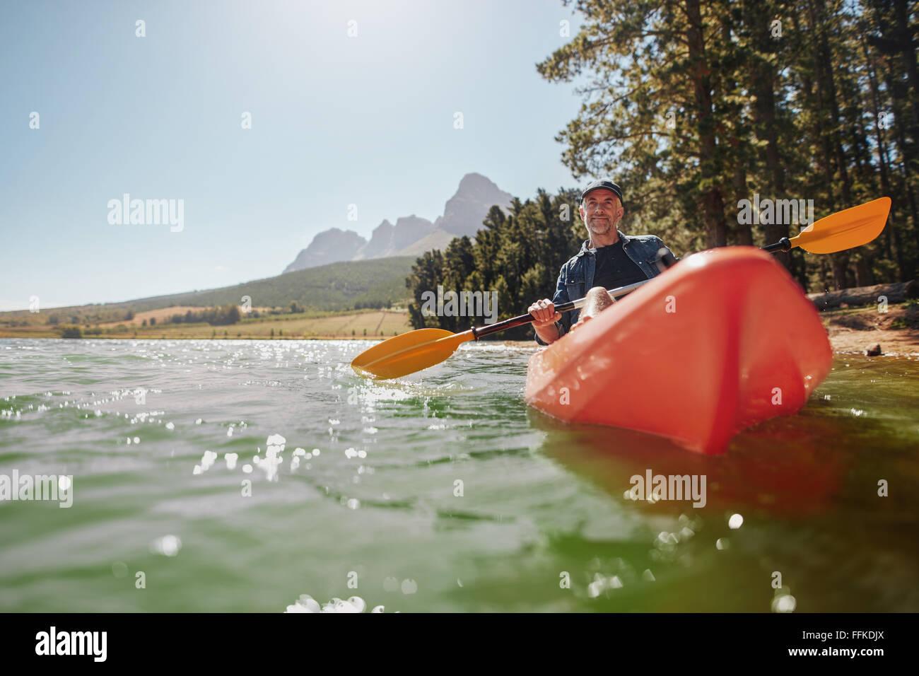 Vista trasera de un hombre senior canoa en un lago en un día soleado. Hombre Senior remando con el kayak. Imagen De Stock