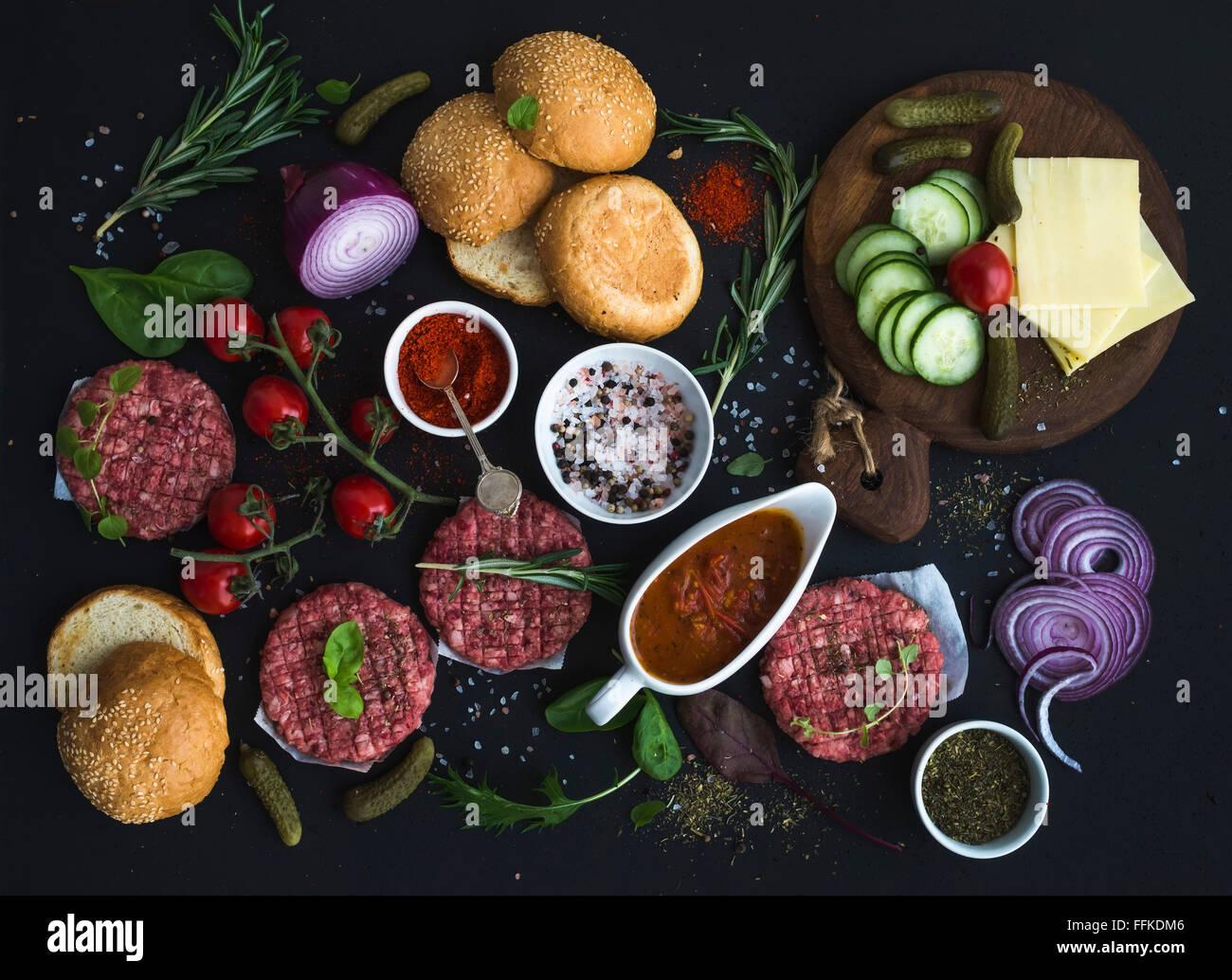 Ingredientes para cocinar hamburguesas. Carne molida cruda las croquetas de carne, bollos, cebolla roja, tomates Imagen De Stock
