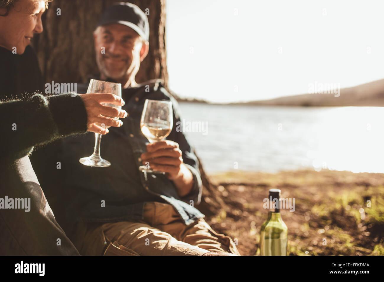 Close Up retrato de pareja senior bebiendo vino mientras camping cerca de un lago. Se centran en manos sosteniendo una copa de vino. Foto de stock