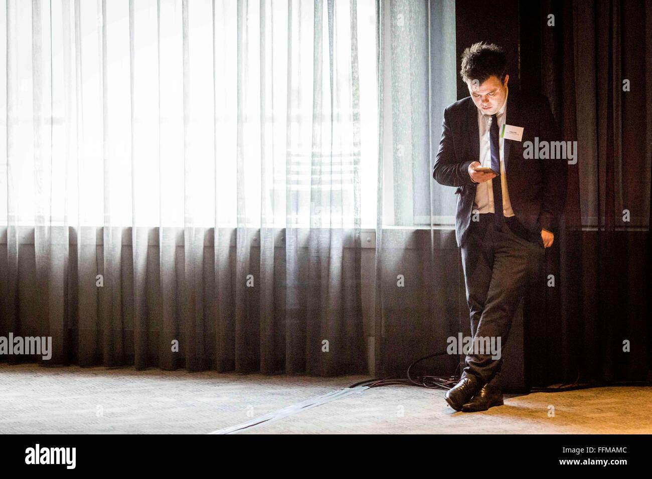 Un hombre en un traje que luce en su teléfono móvil Imagen De Stock
