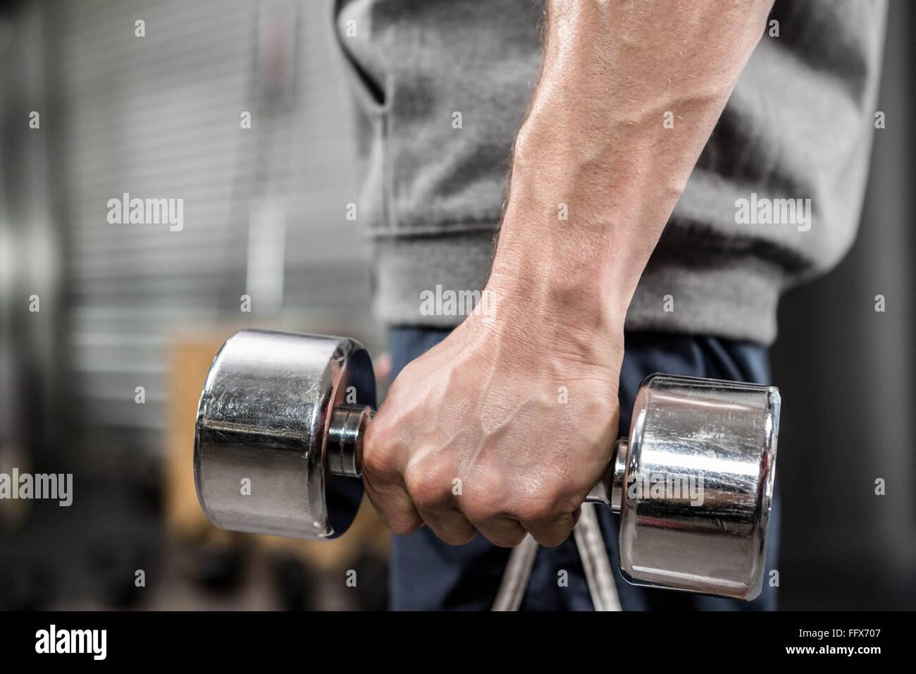 El hombre muscular con puente gris celebración pesa Imagen De Stock