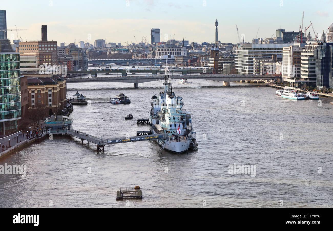 HMS Belfast sobre el río Támesis en Londres ciudad con el Puente de Londres en el fondo Foto de stock