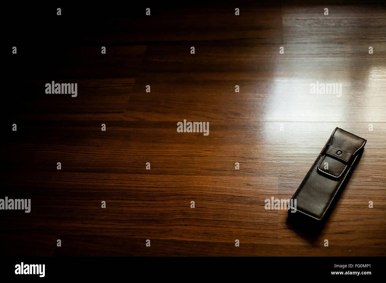 Un alto ángulo de vista de cuero Cubierta de teléfono sobre un piso de madera Imagen De Stock