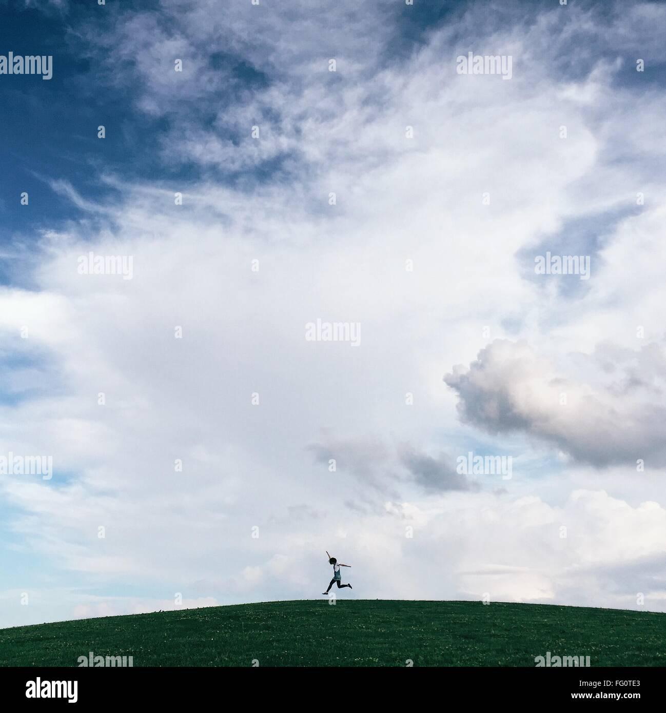 Ángulo de visión baja de persona saltando en grassy hill contra el cielo nublado Foto de stock