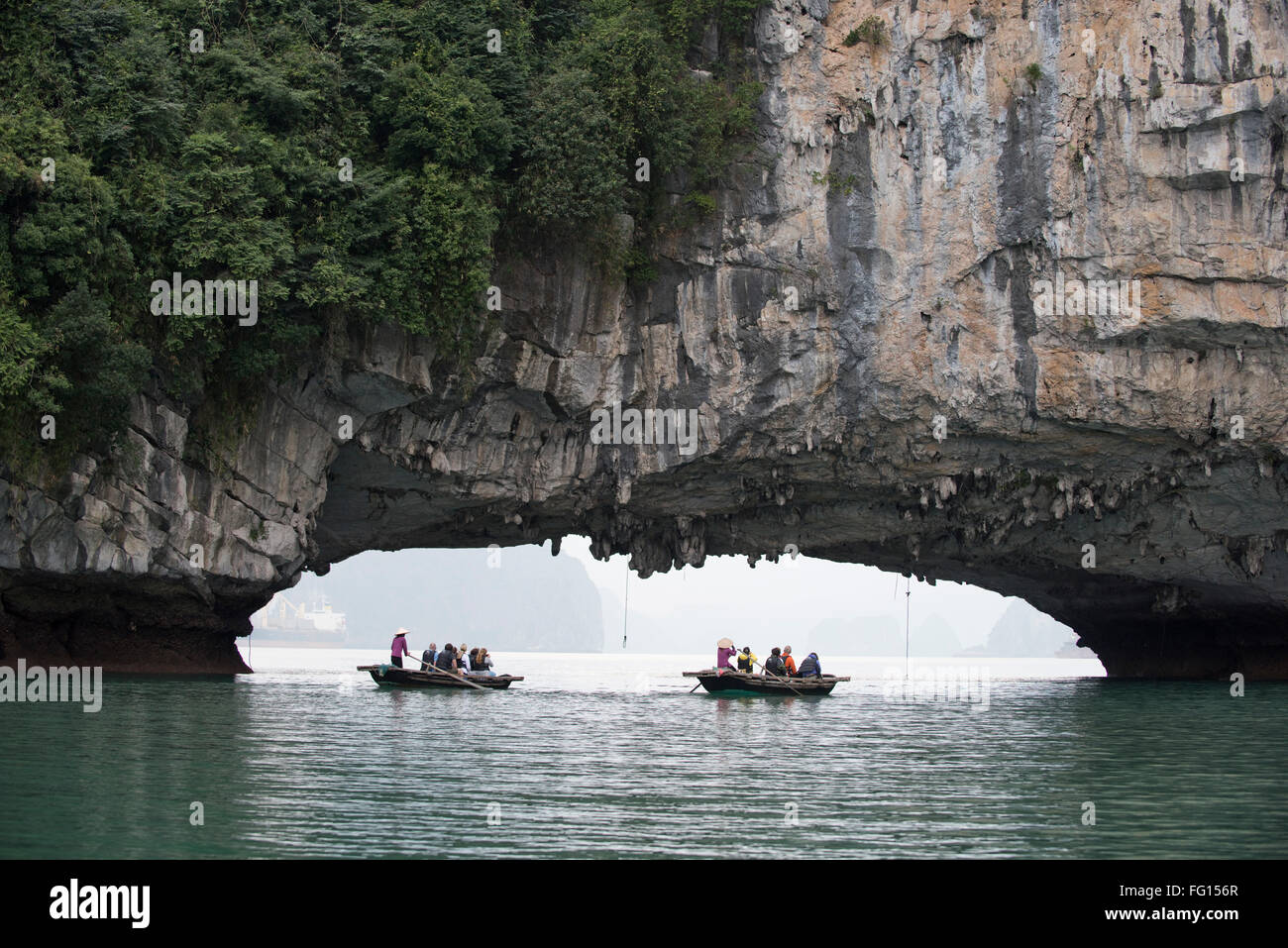 Los barcos turísticos remando cerca de un túnel cortado por el mar en un karst calizo en Halong Bay en Imagen De Stock