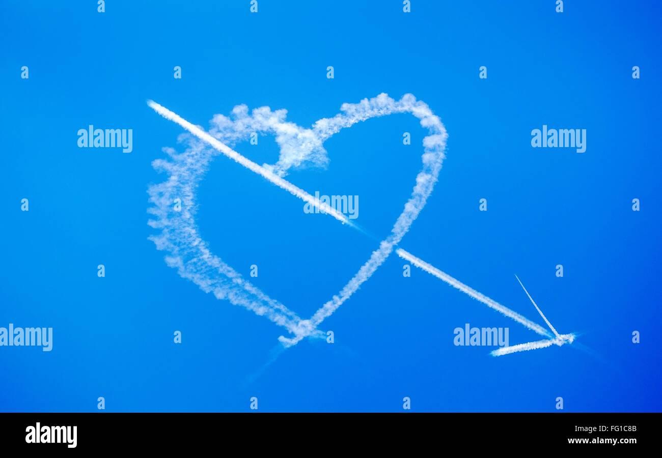 Ángulo de visión baja de flecha y Corazón Vapor Trail en Blue Sky Imagen De Stock