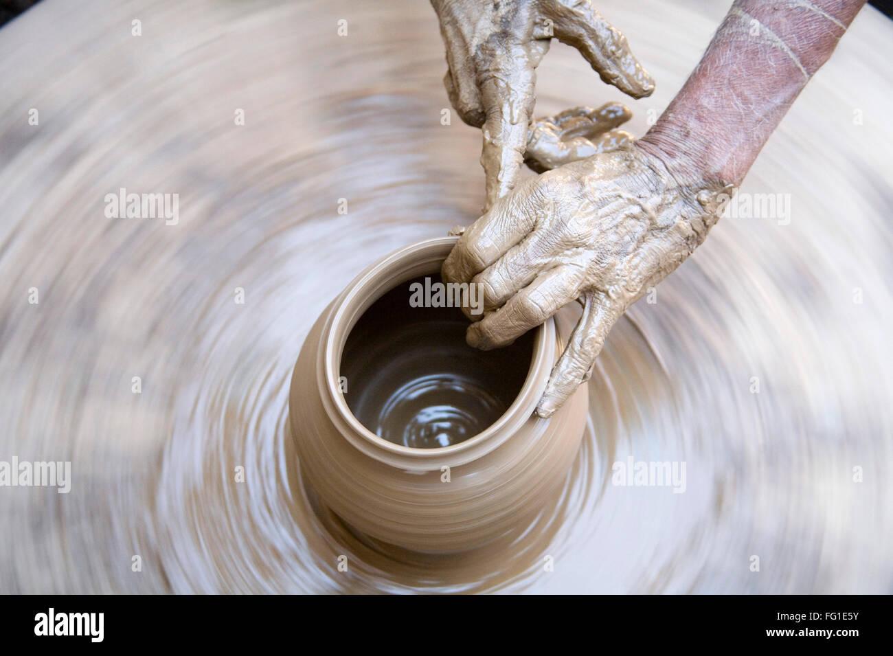 Alfarería , alfarero manos fangosas haciendo olla de arcilla dando forma a la rueda giratoria , Dilwara , Udaipur , Rajastán , India , Asia Foto de stock