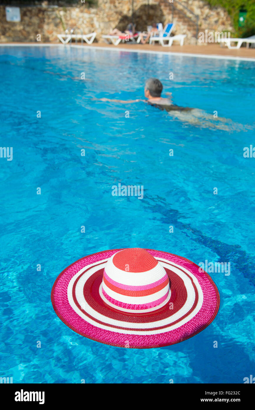 Piscina de lujo con rosa sombrero para el sol femenino Foto de stock