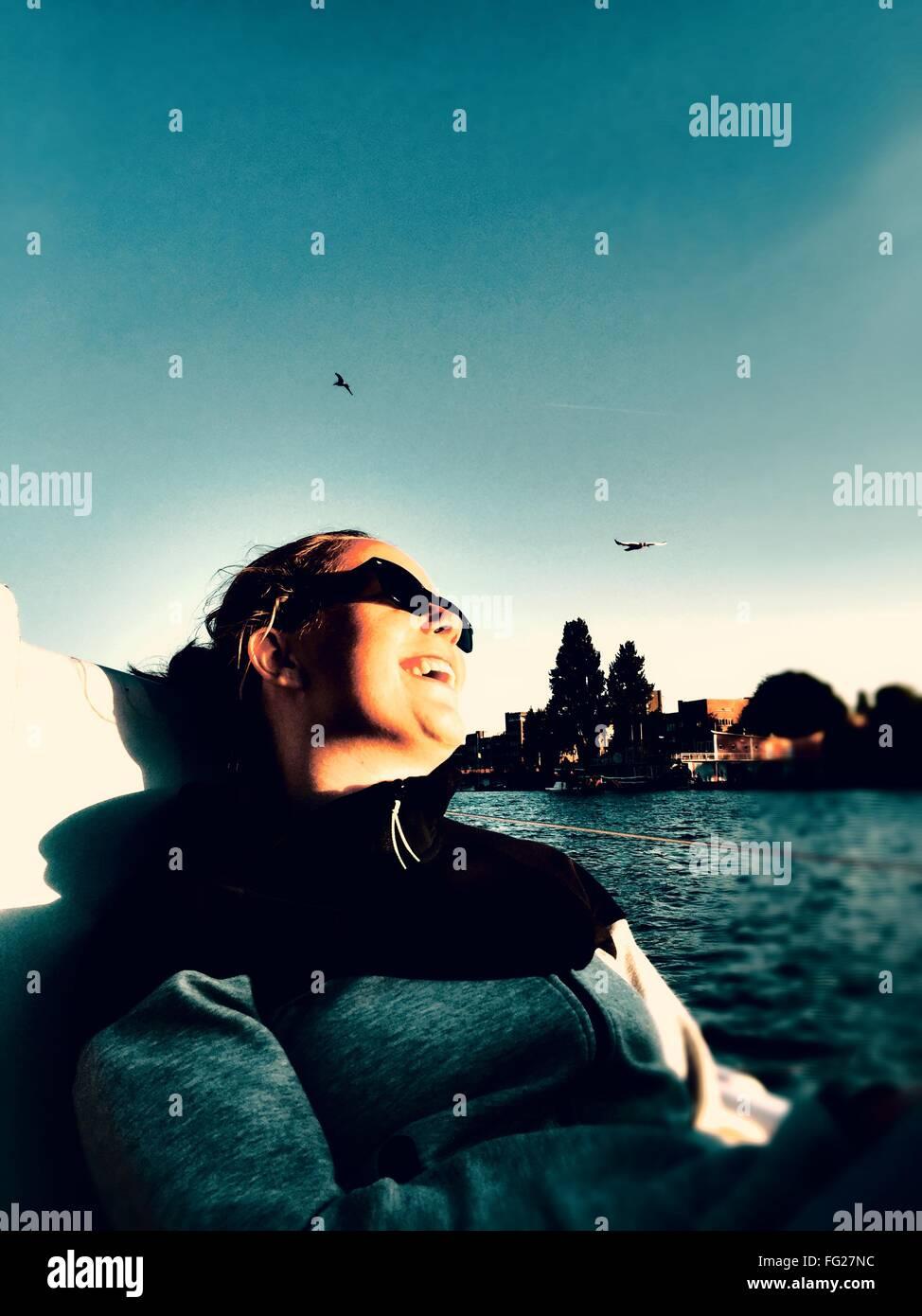 Ángulo de visión baja de Mujer sentada en buque náuticas en el río Imagen De Stock