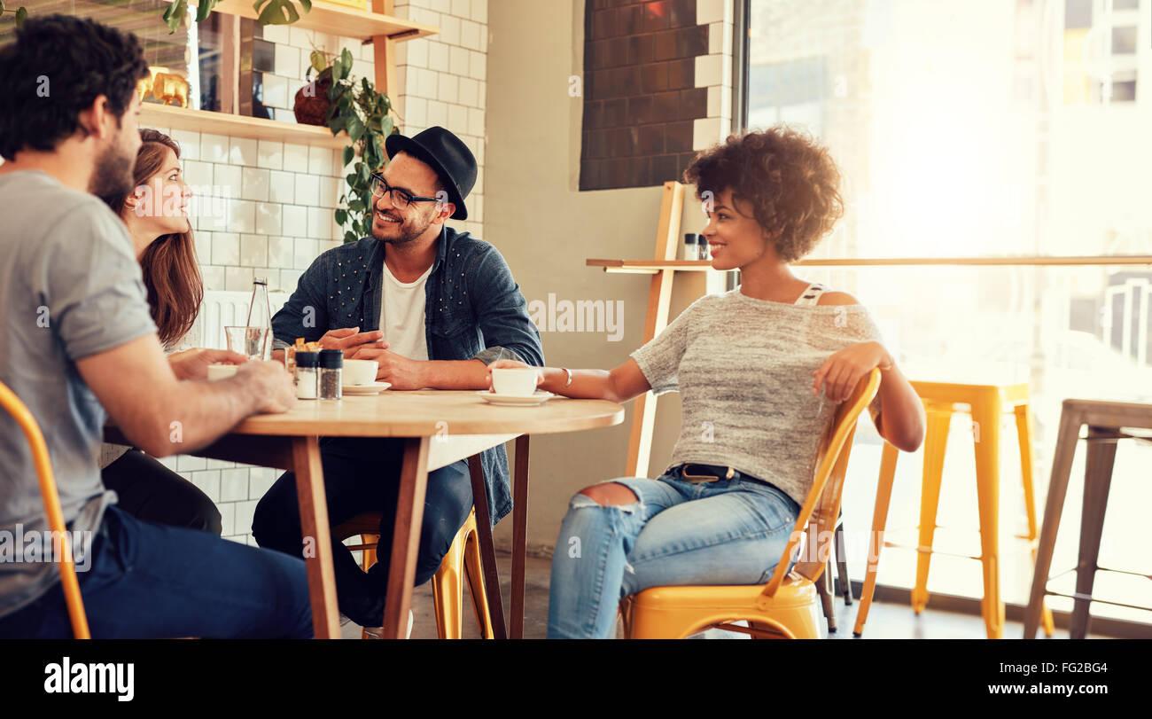 Retrato de un joven grupo de amigos en un café. Hombres y mujeres jóvenes sentados en la mesita de café Imagen De Stock