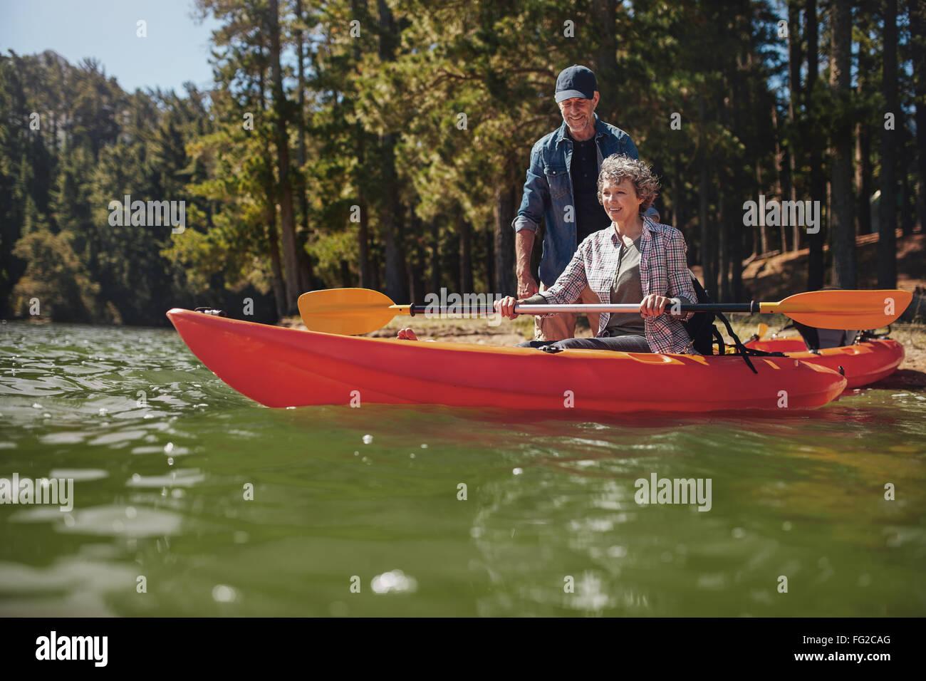 Retrato de hombre maduro, dar instrucciones a la mujer remando un kayak en el lago. Mujer Senior recibiendo clases Imagen De Stock