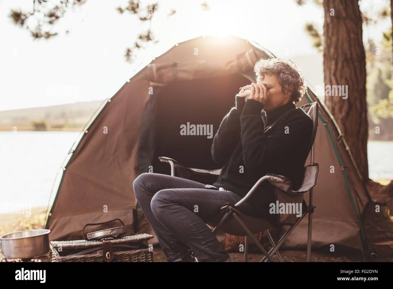 Retrato de mujer madura, sentada en una silla en el camping de beber café. Mujer caucásica acampar en Imagen De Stock