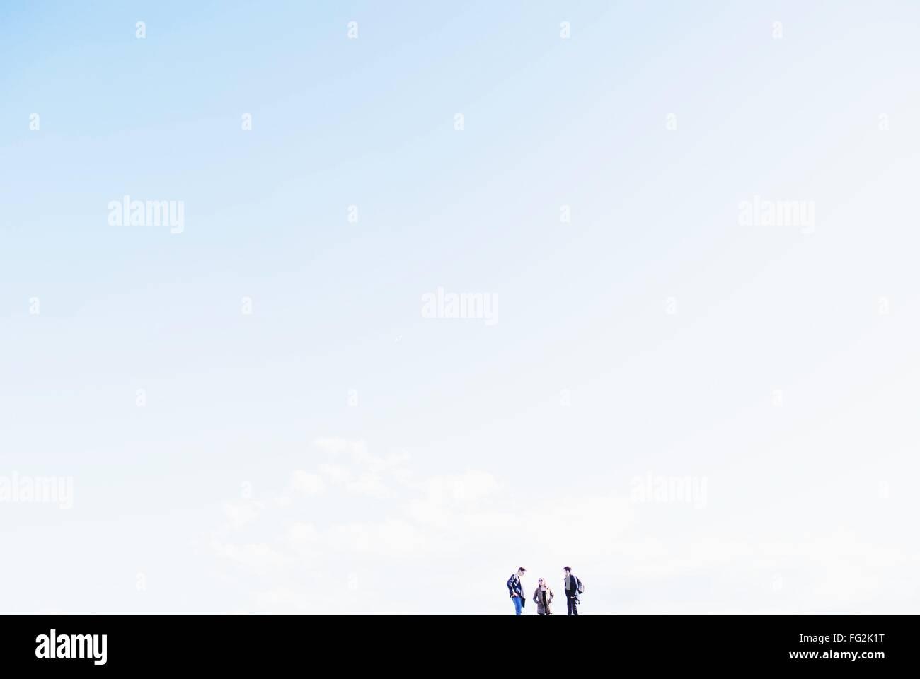 Ángulo de visión baja de amigos que estaban de pie en la colina contra el cielo Foto de stock