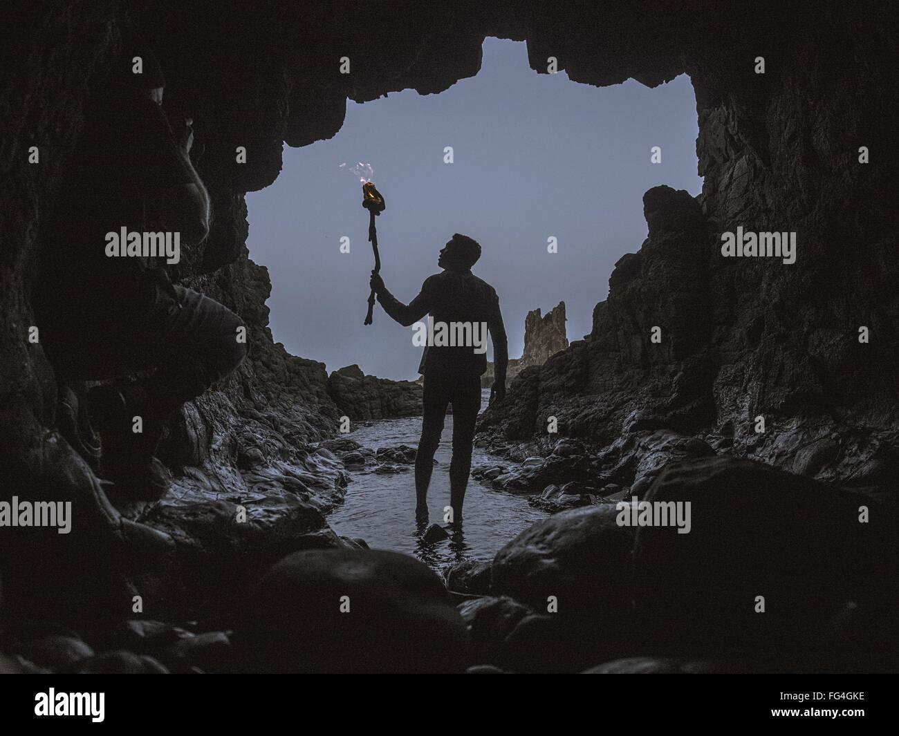 Hombre con antorchas caminando en una cueva. Imagen De Stock