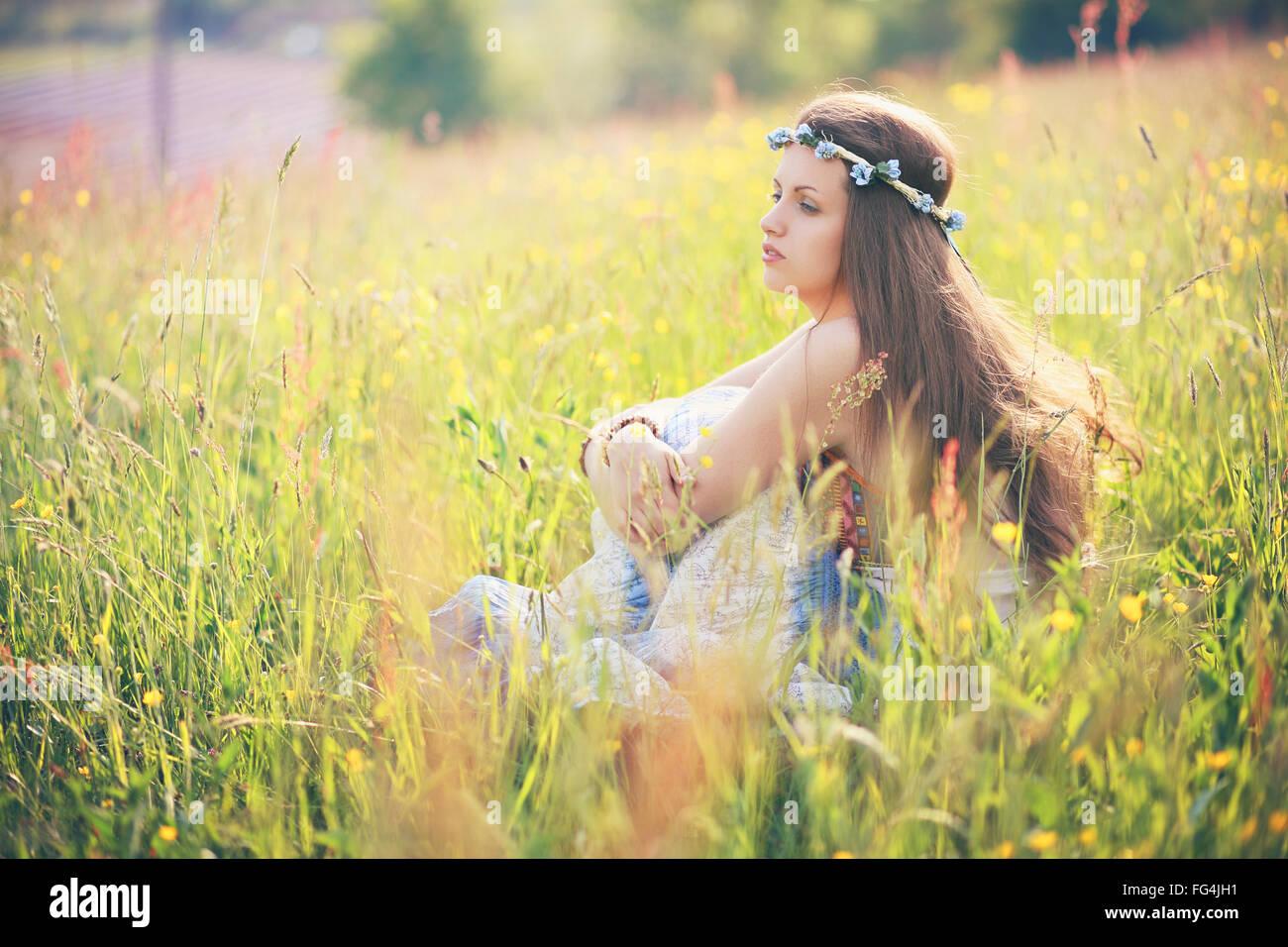 Mujer joven disfrutando de la primavera en el campo de flores . Vestido de hippie y gitano Imagen De Stock