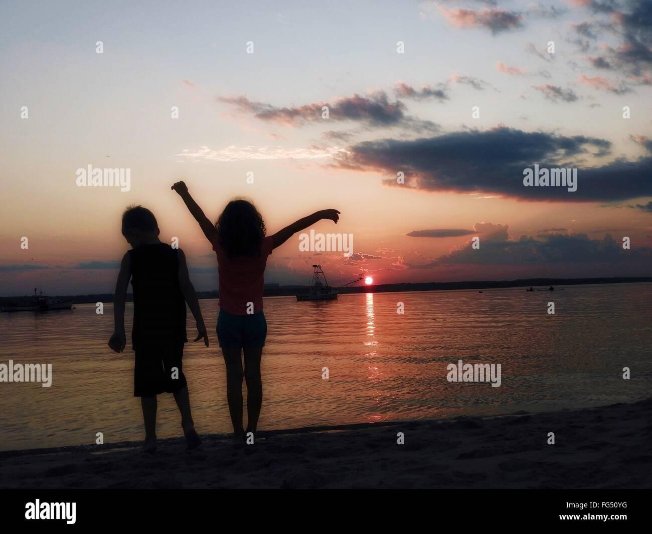 Silueta Hermanos de pie en la playa durante la puesta de sol Imagen De Stock