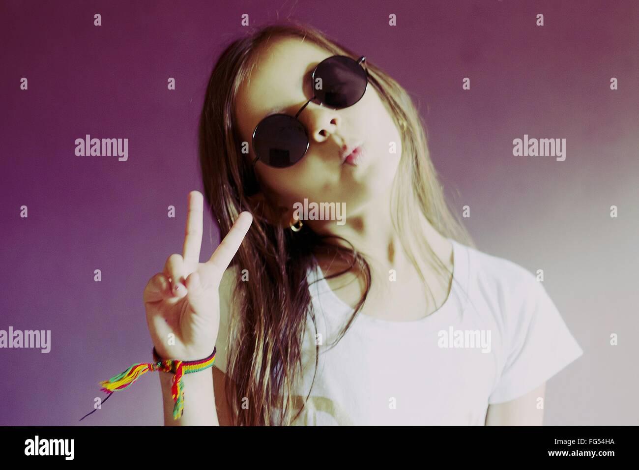 Retrato de chica con gafas Retro gesticulando signo de paz contra la pared en casa Imagen De Stock