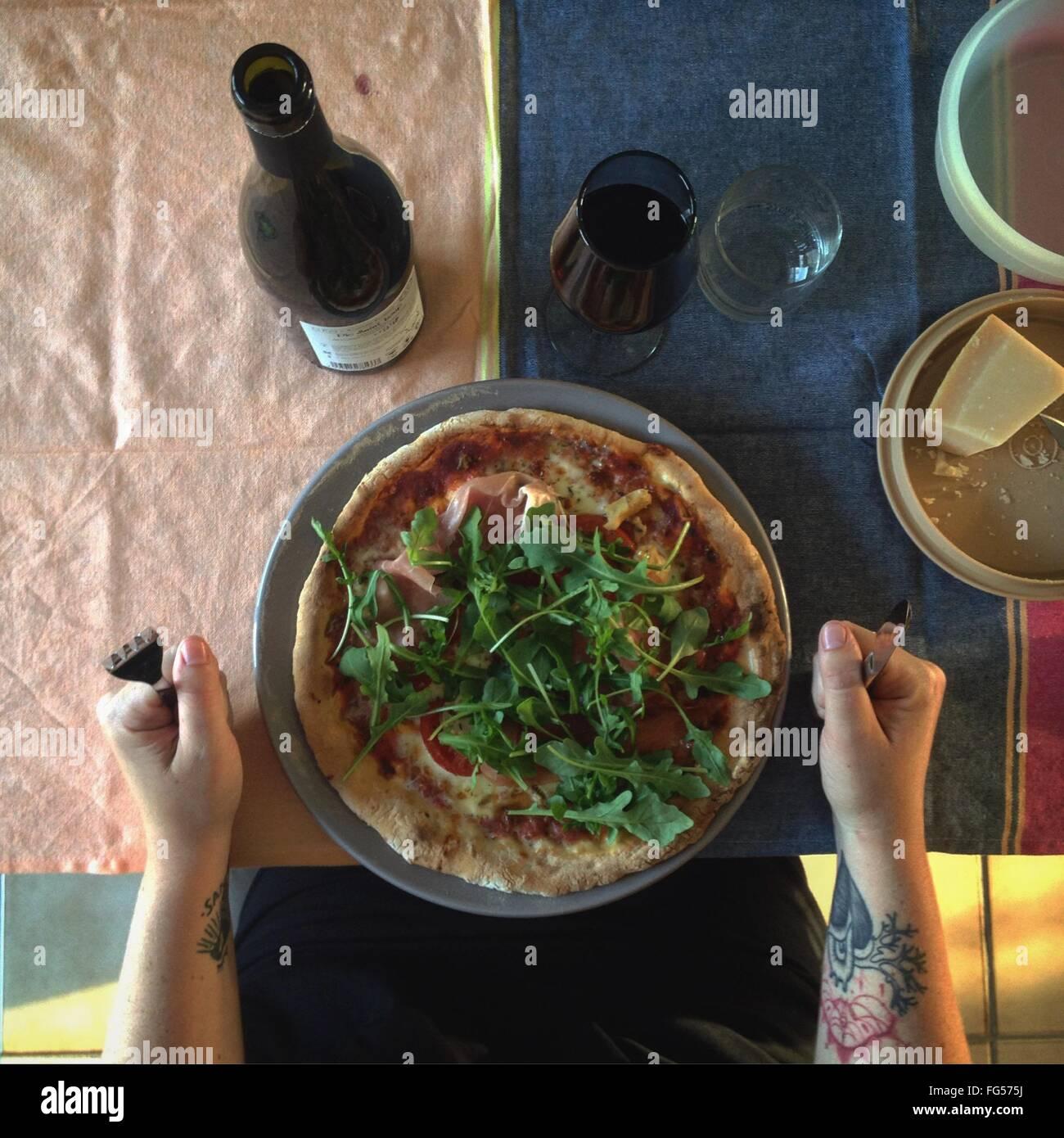Imagen recortada de la mano con la pizza y el vino en la mesa Imagen De Stock