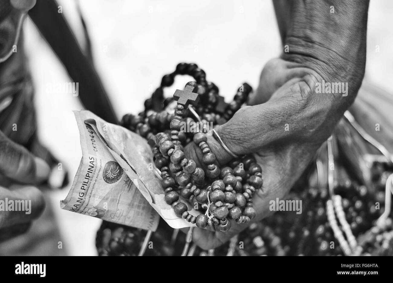 Recorta mano sosteniendo Rosario y dinero. Imagen De Stock