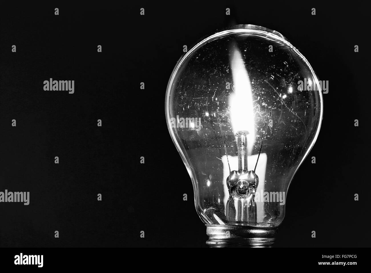 Primer plano de encendida la bombilla eléctrica contra fondo negro Imagen De Stock