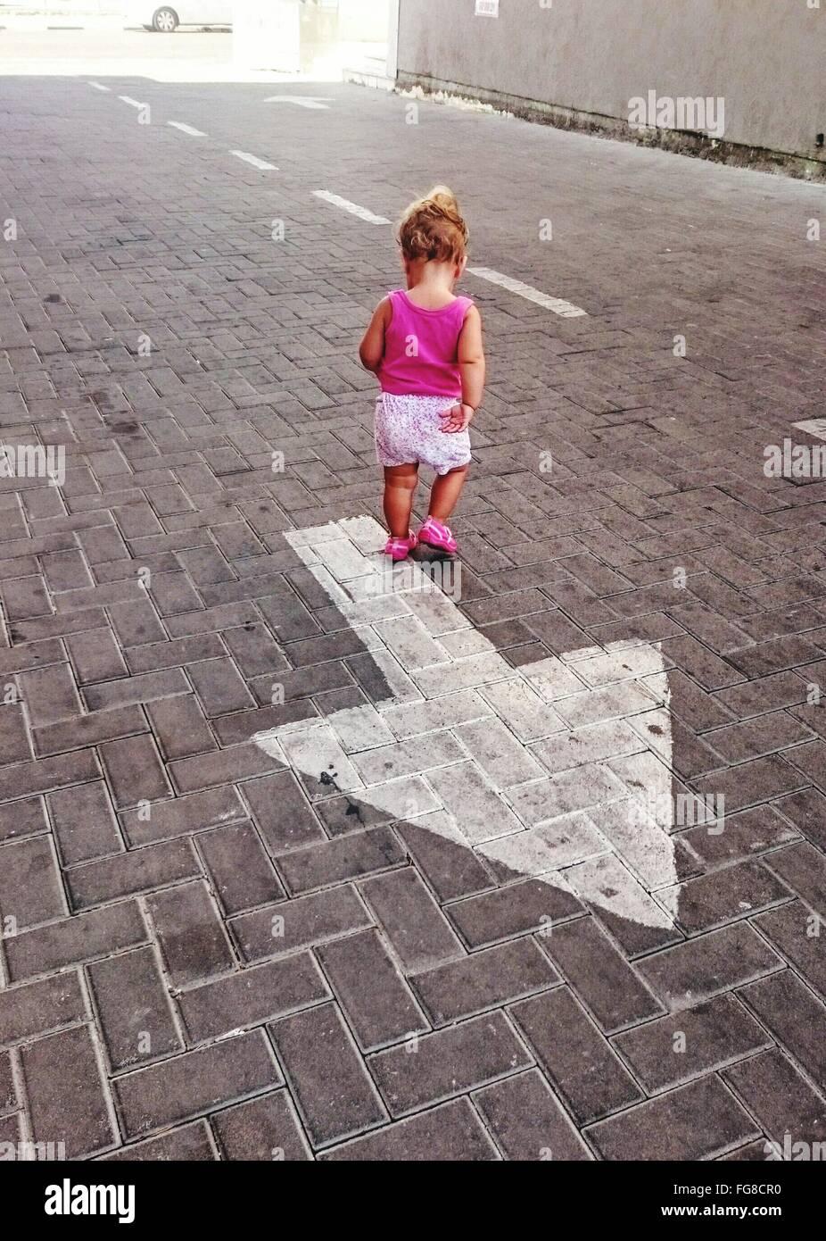 Vista trasera de la niña caminando sobre el símbolo de la flecha en la calle de adoquines Imagen De Stock