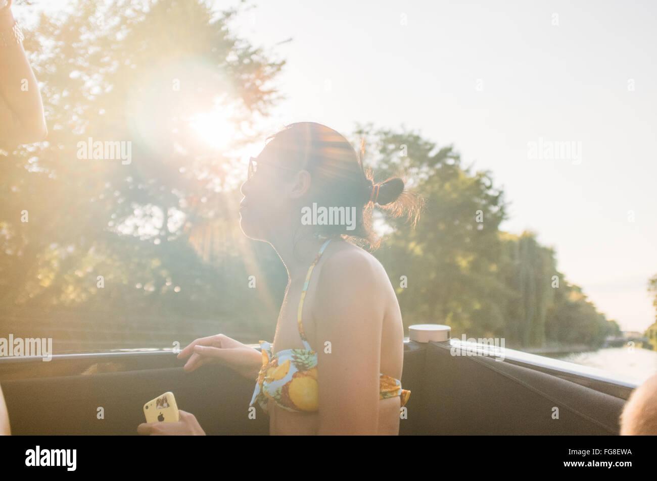 Mujer sentada y disfrutando en barco en el río Imagen De Stock