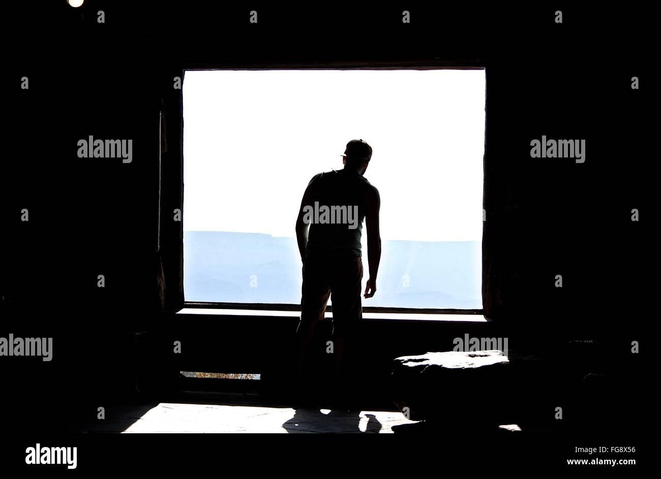 Vista trasera del hombre por la ventana Imagen De Stock