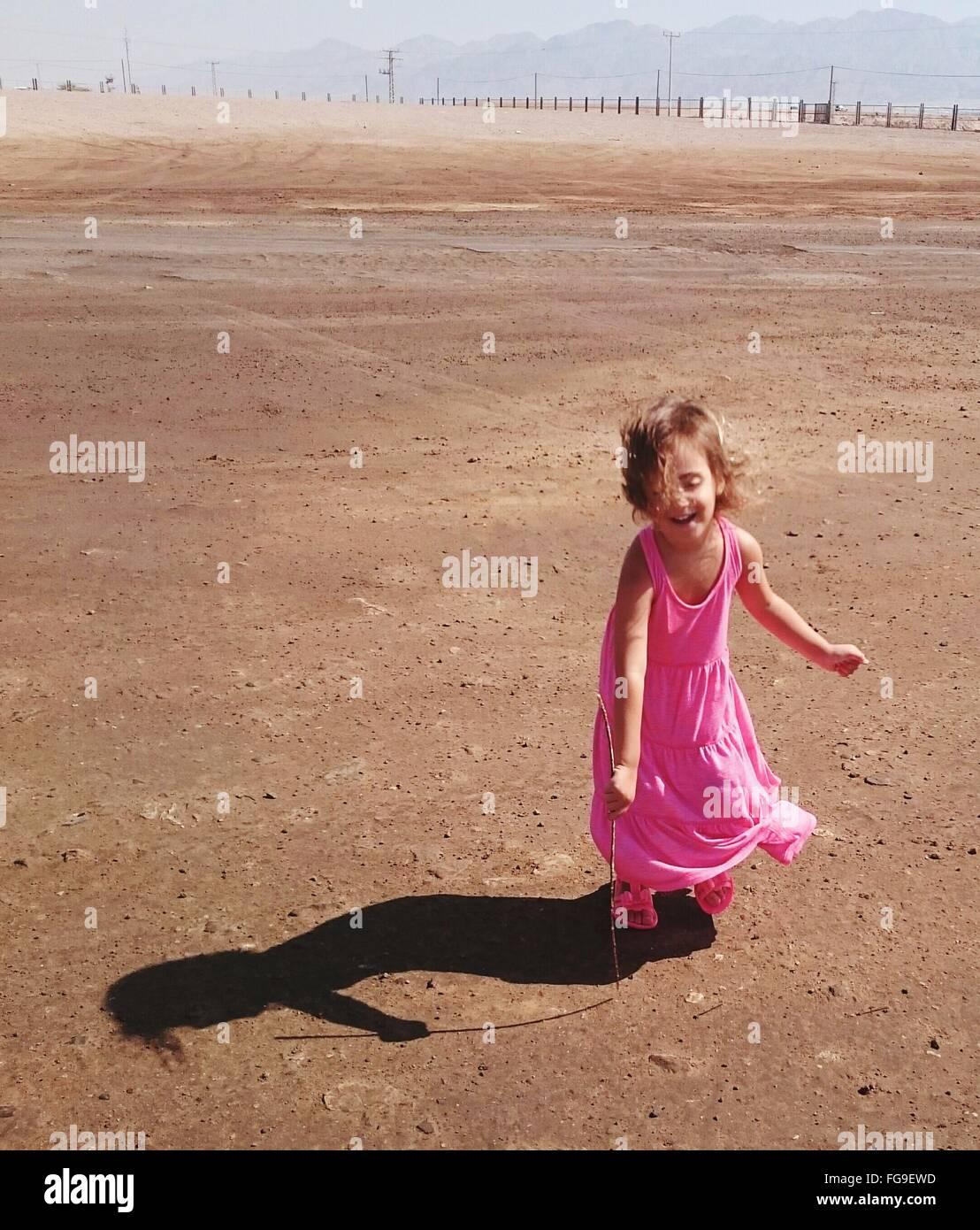 Niña alegre disfrutando en el desierto, en día soleado Imagen De Stock