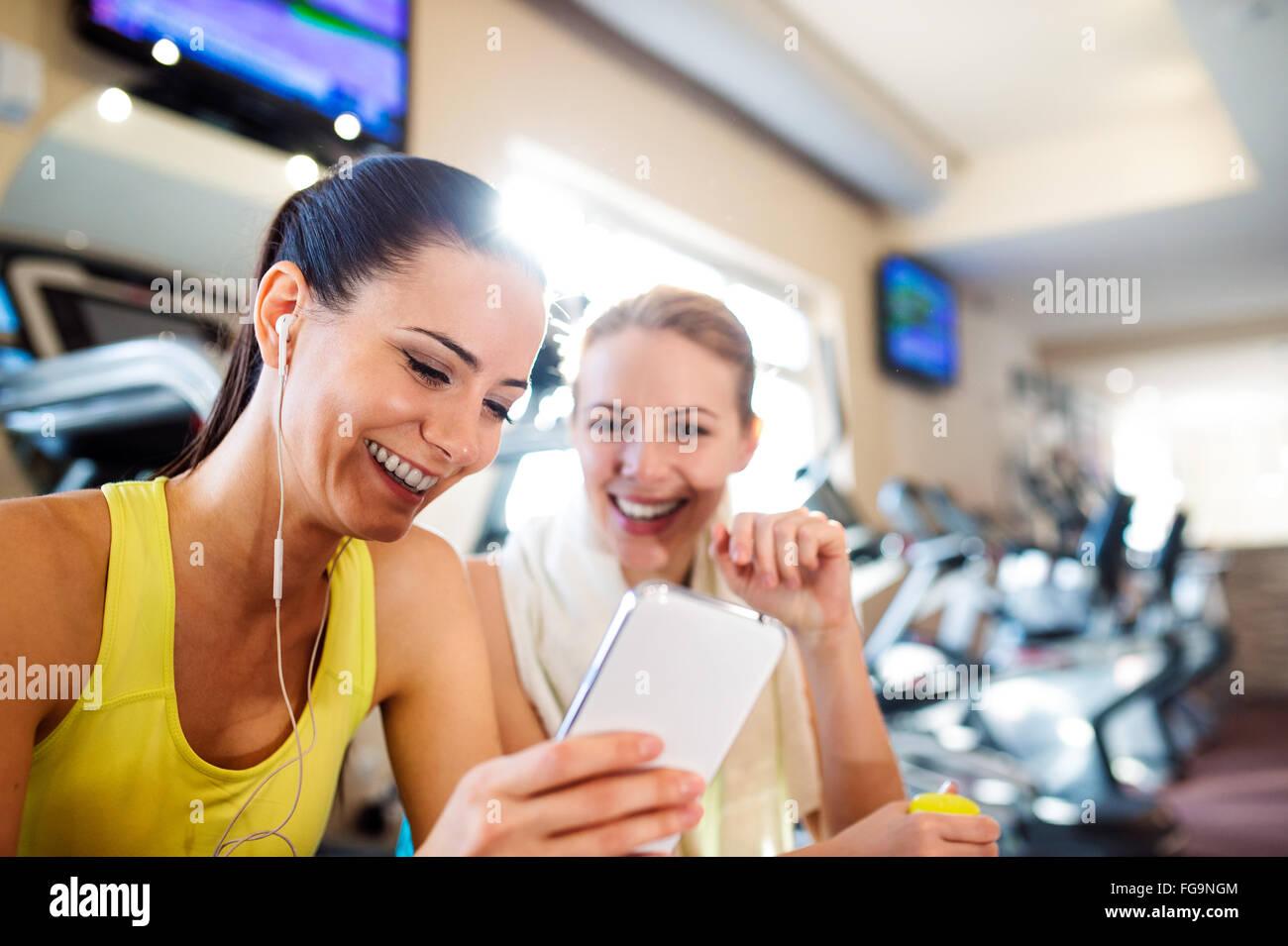 Colocar dos atractivas mujeres en gimnasio con teléfonos inteligentes. Imagen De Stock