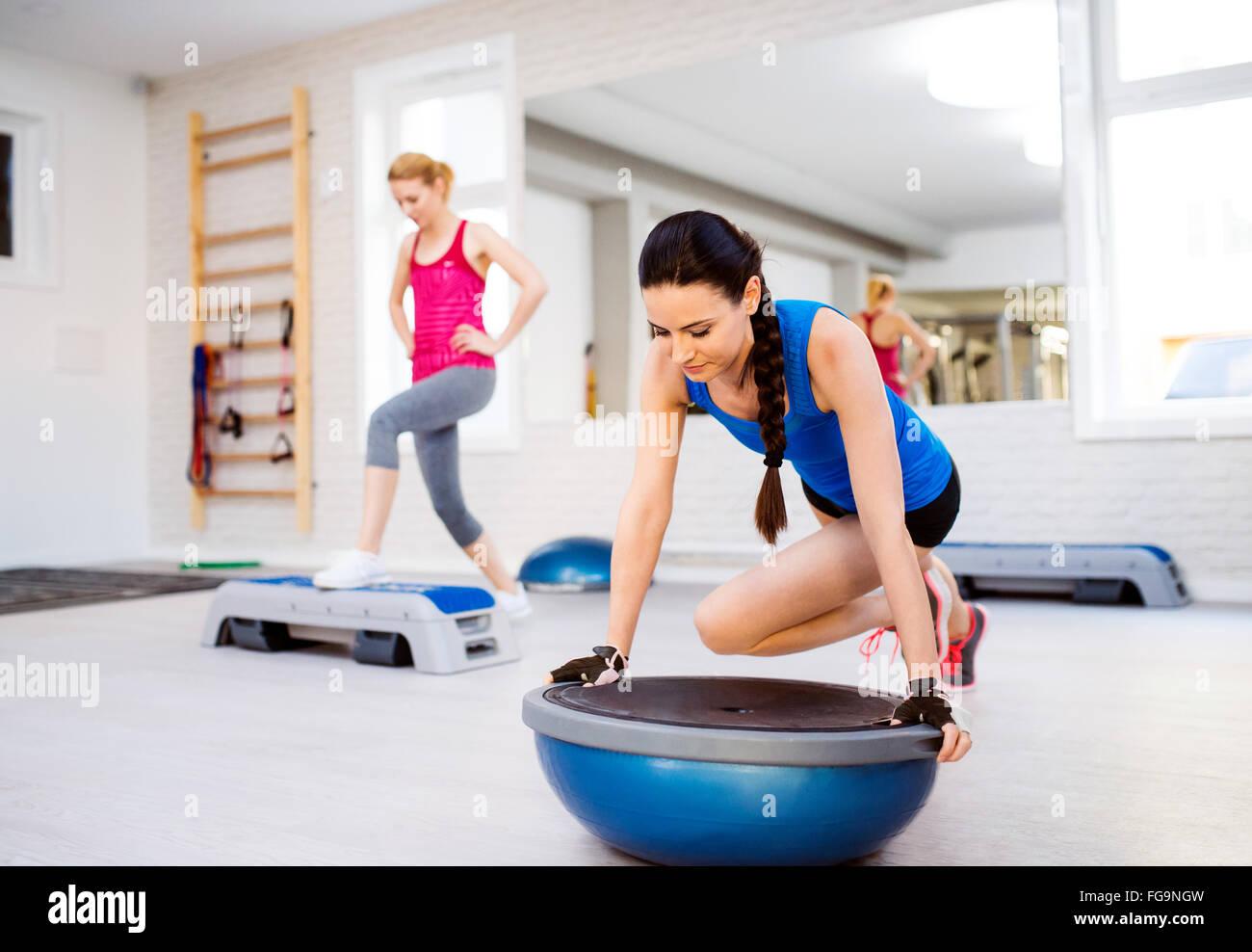 Colocar dos mujeres atractivas en el gimnasio haciendo diversos ejercicios Imagen De Stock