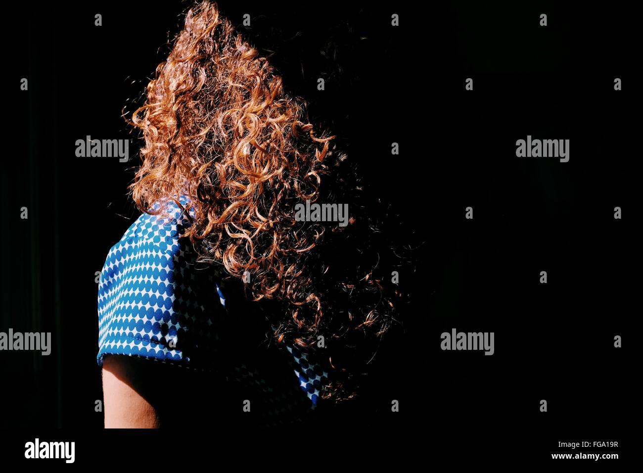 Mujer con cabello castaño rizado en la luz del sol Imagen De Stock