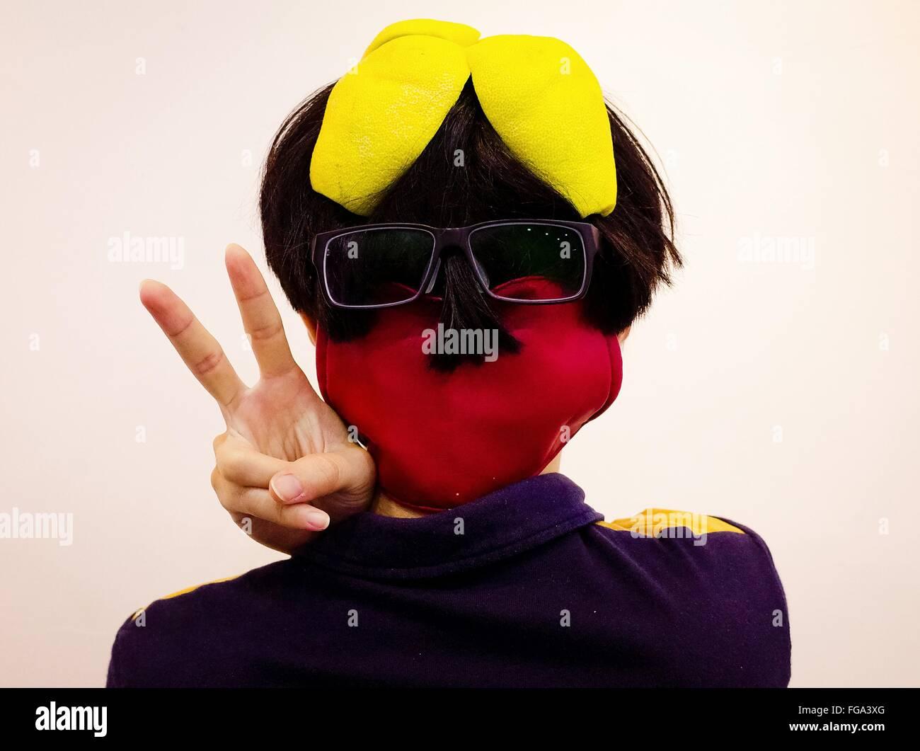 Vista trasera de la persona con gafas y máscara mostrando signos de paz contra el fondo blanco. Imagen De Stock