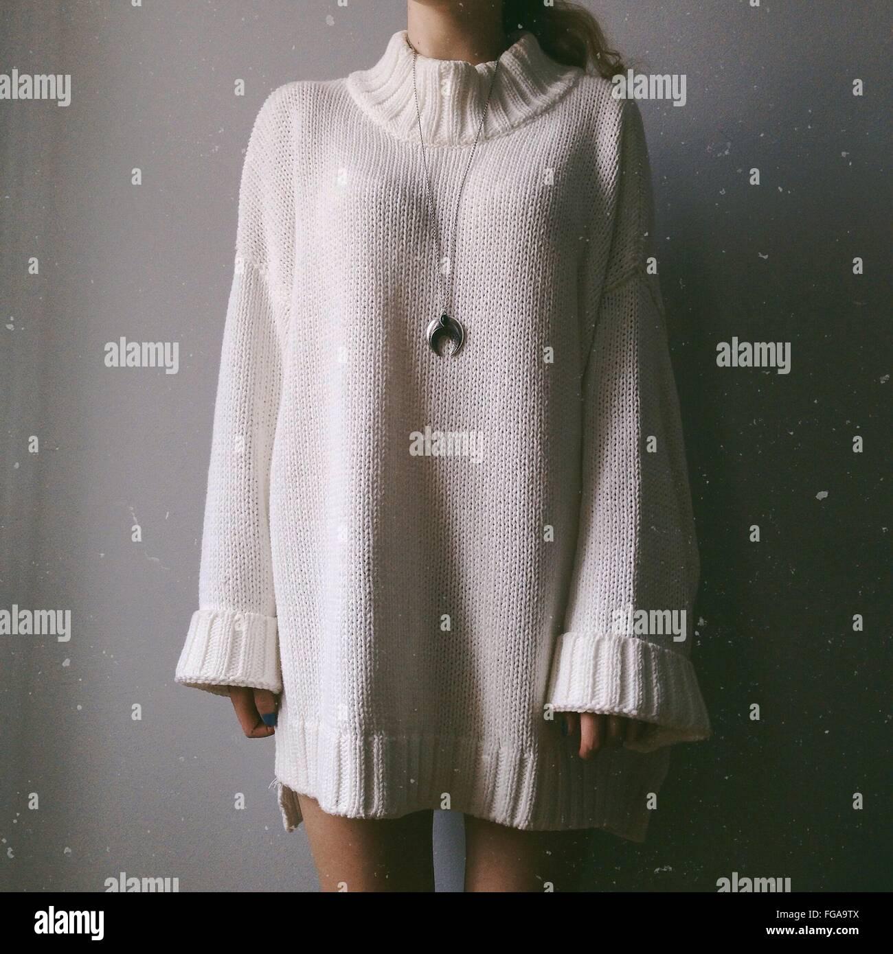 Sección media de la mujer en el suéter de pie contra la pared Imagen De Stock