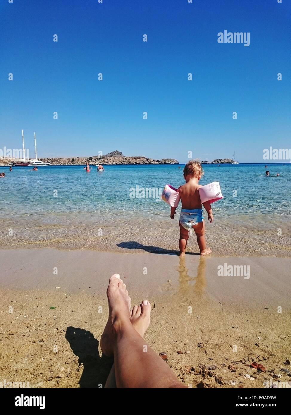 Recorta las piernas del hombre delante de un niño llevando agua alas por mar contra el cielo Imagen De Stock