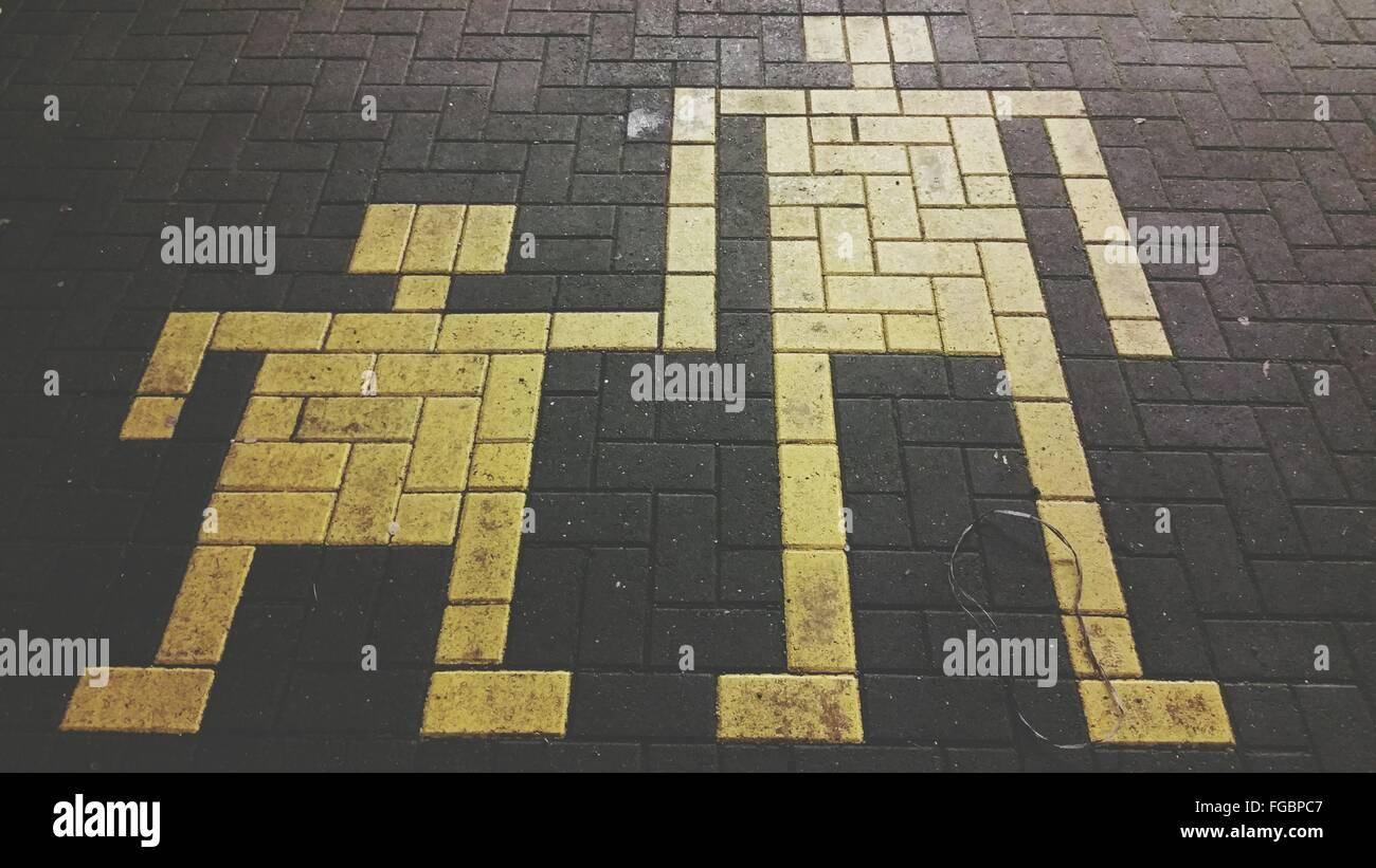 Un alto ángulo de visualización de adoquines pintados de amarillo sendero Foto de stock