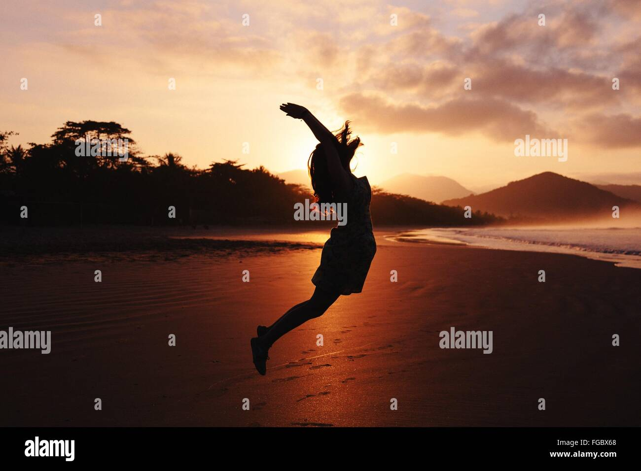 Vista lateral de la silueta de la mujer con los brazos levantados saltando en la playa Imagen De Stock