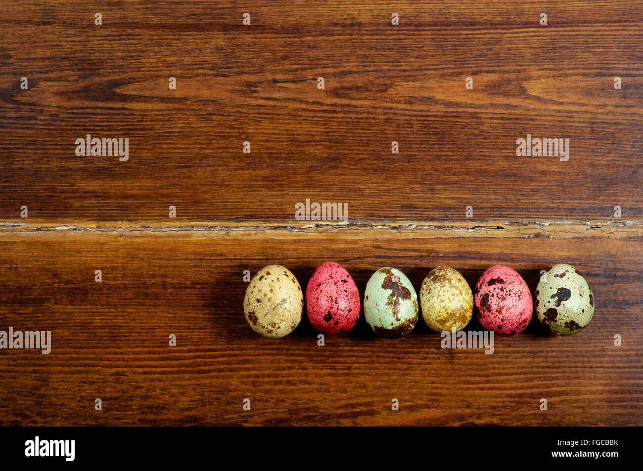 Varios coloridos huevos de codorniz sobre fondo de madera Foto de stock