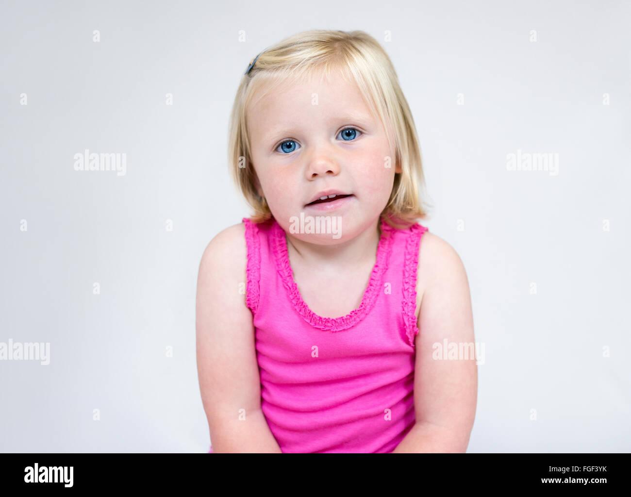 Retrato de una joven con corta el pelo rubio y ojos azules vistiendo un chaleco rosa sonriendo Foto de stock