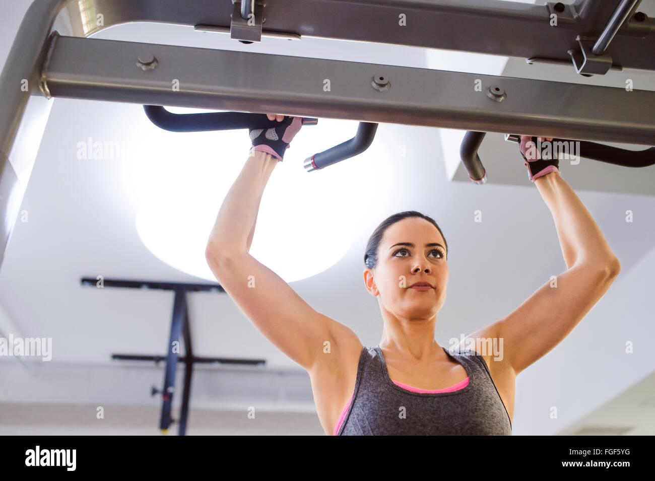 Mujer en el gimnasio haciendo ejercicios de armas en una máquina Imagen De Stock