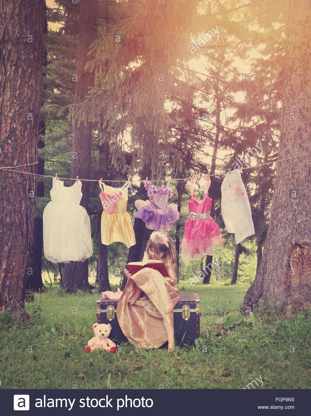 Es una chica vestida como una princesa leyendo un libro en el bosque con trajes colgando de un tendedero para una Imagen De Stock