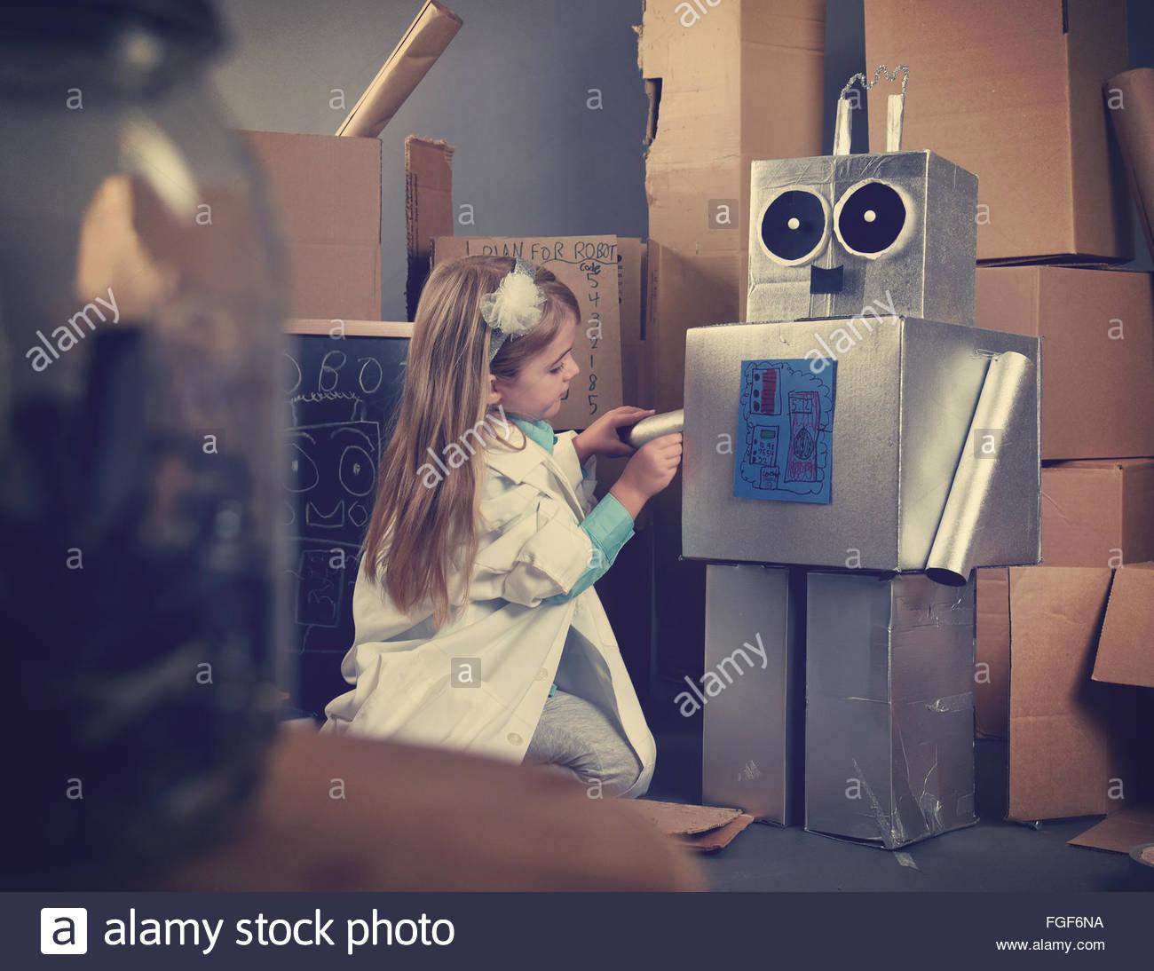 Un estudiante de ciencia es inventar un robot de metal fuera de cajas de cartón con herramientas. Utilizarlo Imagen De Stock