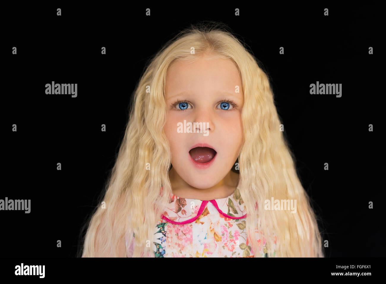 Joven con largo pelo rubio sorprendió con una expresión de pie contra un fondo negro Foto de stock