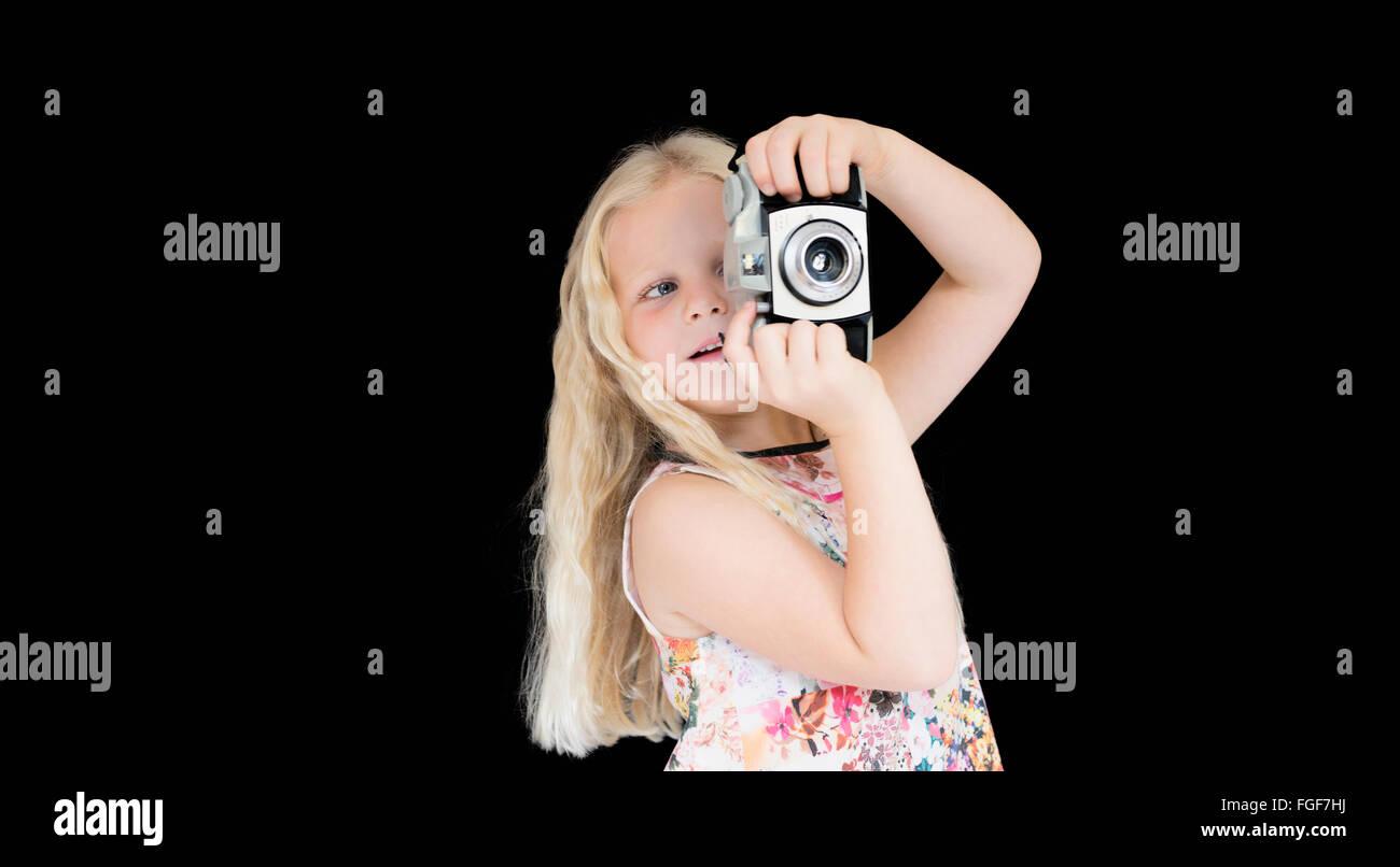 Joven con largo pelo rubio tomando una fotografía con una cámara vintage de pie contra un fondo negro Foto de stock
