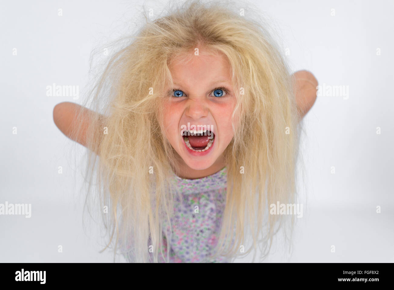 Niña con cabello rubio desordenado gritando Foto de stock