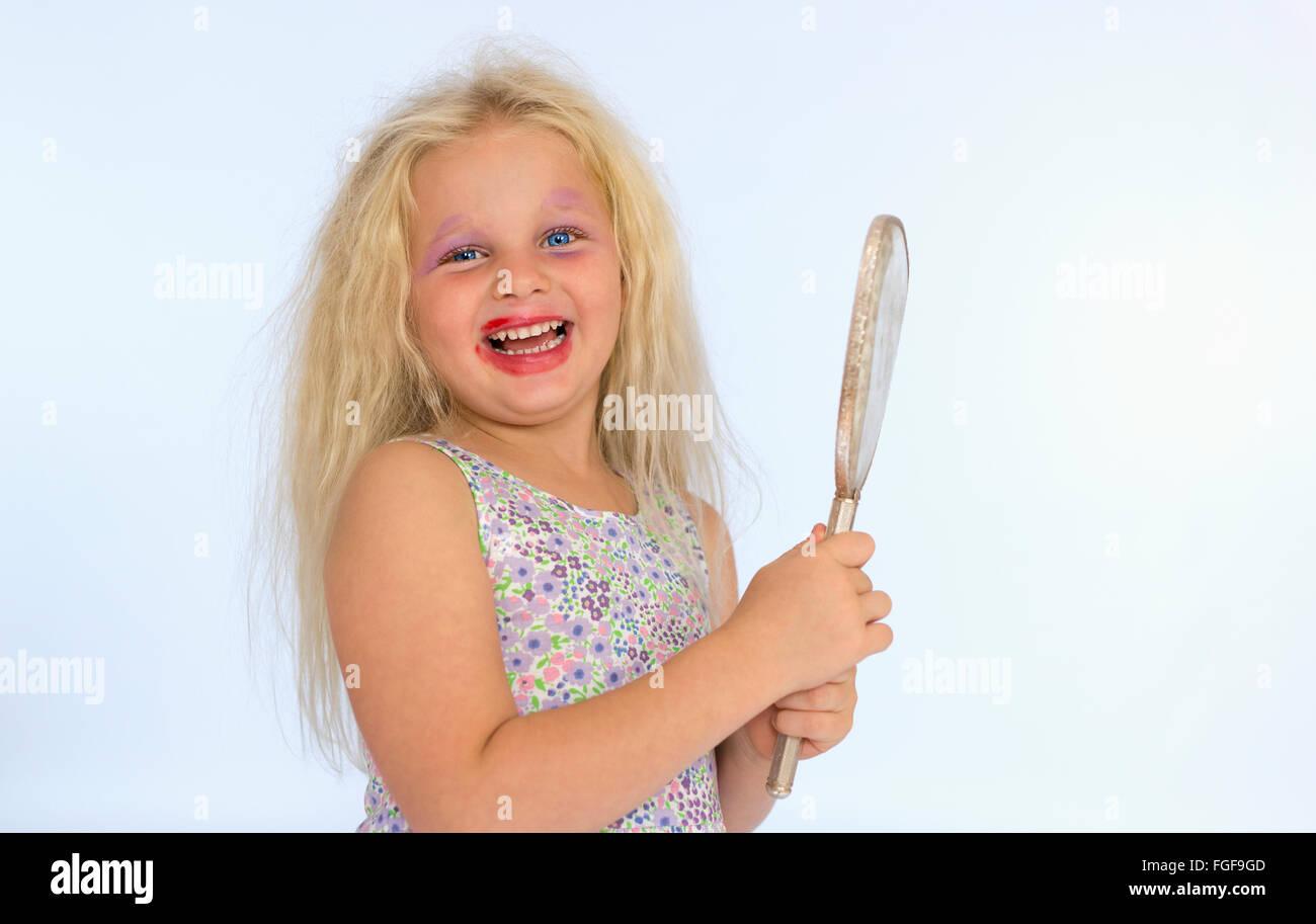 Muchacha con cabello rubio vistiendo maquillaje manchado sosteniendo un espejo, riendo Foto de stock