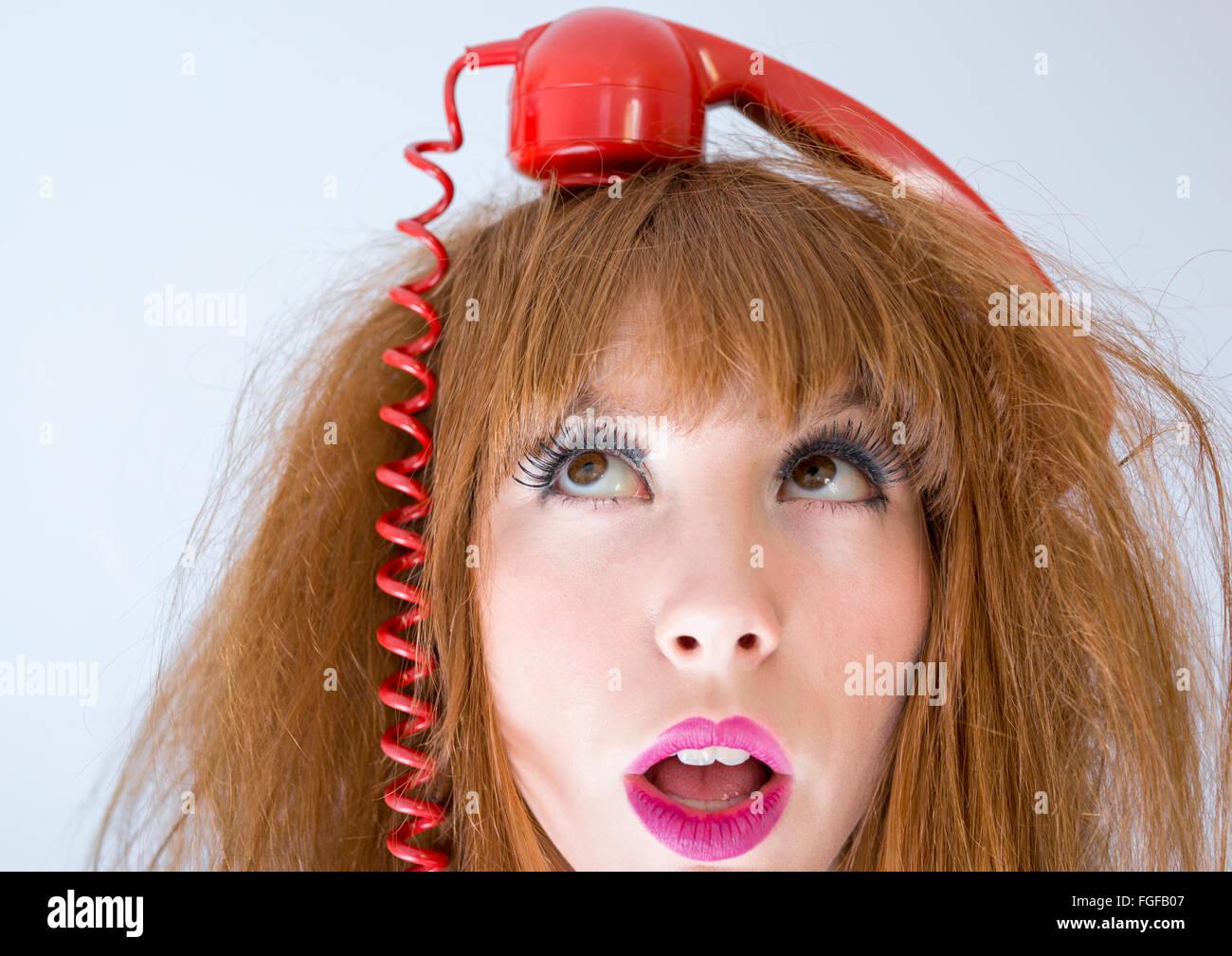 Mujer con un auricular de teléfono rojo retro equilibrio sobre la parte superior de la cabeza Foto de stock