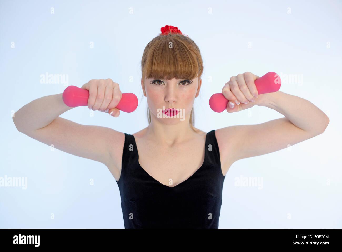Mujer con el cabello marrón largo sudor vistiendo una diadema rosa sosteniendo mancuernas ejercicio Imagen De Stock